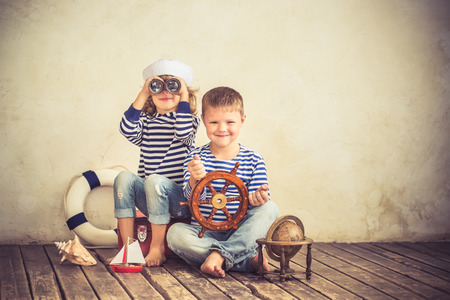 Photo pour Children playing with vintage nautical things. Kids having fun at home. Travel and adventure concept. Retro toned image - image libre de droit
