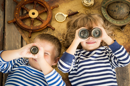Foto de Happy kids playing with nautical things. Children having fun at home. Travel and adventure concept. Unusual high angle view portrait - Imagen libre de derechos