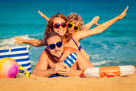 Photo pour Happy family playing at the beach. Summer vacation concept - image libre de droit