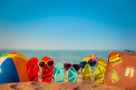 Photo pour Flip-flops, beach ball and suitcase on the sand. Summer vacation concept - image libre de droit