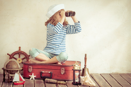 Foto de Happy child playing with vintage nautical things. Kid having fun at home. Summer sea dream and imagination. Adventure and travel concept. Retro toned image - Imagen libre de derechos