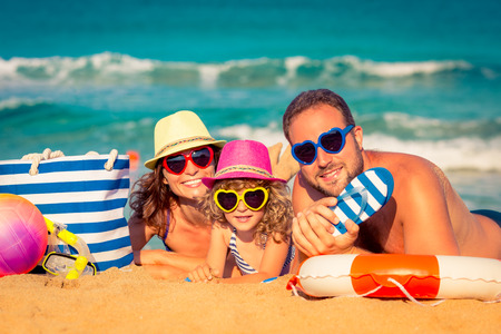 Foto per Happy family playing at the beach. Summer vacation concept - Immagine Royalty Free