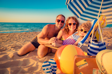 Foto de Happy family sitting on the sunbed. Man, woman and child having fun at the beach. Summer vacation concept - Imagen libre de derechos