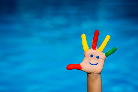 Smiley on hand against blue water background. Summer vacation concept