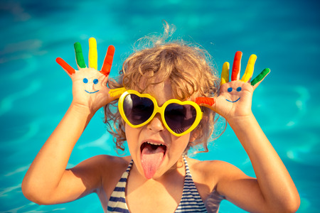 Foto de Funny child with drawing smiley on hands in swimming pool. Summer vacation concept - Imagen libre de derechos