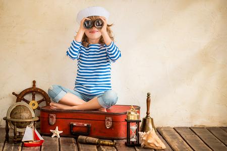 Foto de Happy child playing with vintage nautical things. Kid having fun at home. Summer sea dream and imagination. Adventure and travel concept. Retro toned image - Imagen libre de derechos