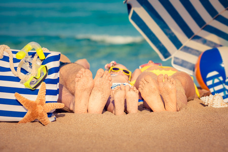 Photo pour Happy family lying on the beach. Summer vacation concept - image libre de droit