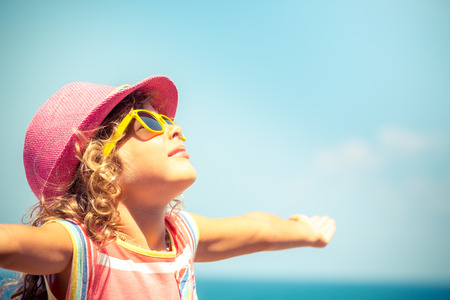 Photo pour Happy child against blue sky background. Summer vacation concept - image libre de droit