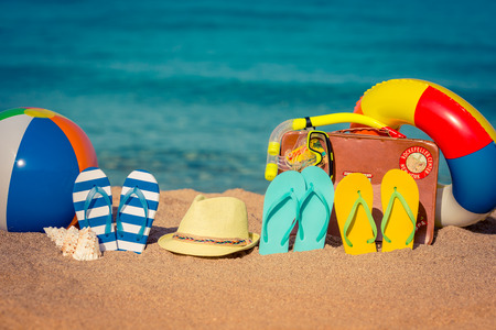 Photo pour Flip-flops, beach ball and vintage suitcase on the sand. Summer vacation concept - image libre de droit