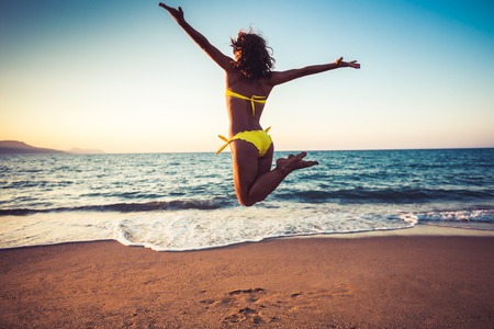 Photo pour Happy young woman jumping on the beach. Summer vacation and freedom concept - image libre de droit