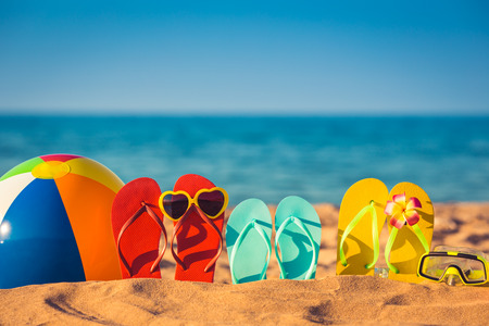 Foto de Flip-flops, beach ball and snorkel on the sand. Summer vacation concept - Imagen libre de derechos
