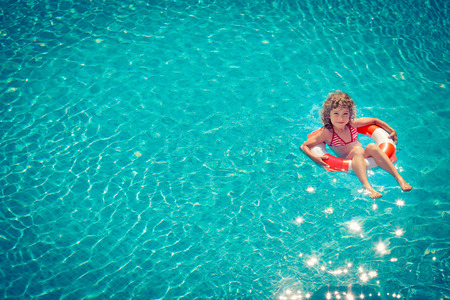 Photo pour Happy child playing in swimming pool. Summer vacation concept. Top view portrait - image libre de droit