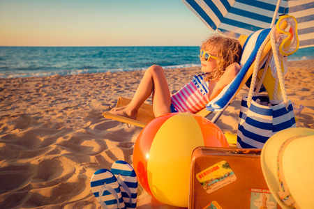 Photo pour Happy child sitting on the sunbed. Funny kid at the beach. Summer vacation concept - image libre de droit