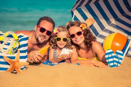 Foto de Happy family lying on the beach. Summer vacation concept - Imagen libre de derechos