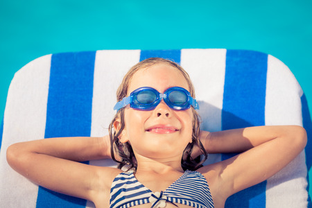 Funny child lying on beach bed against blue water . Summer vacation concept