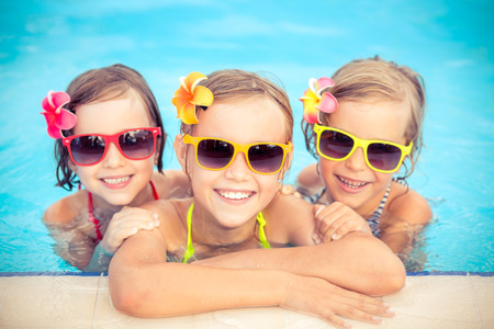 Photo pour Happy children in the swimming pool. Funny kids playing outdoors. Summer vacation concept - image libre de droit