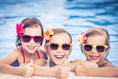 Foto de Happy children showing thumbs up in the swimming pool. Funny kids playing outdoors. Summer vacation concept - Imagen libre de derechos