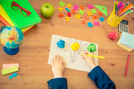 Photo for Child drawing lamp bulb on paper. School items on wooden desk in class. New bright idea concept. Top view - Royalty Free Image
