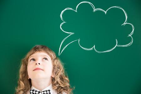 Photo pour School kid in class. Happy child against green blackboard. Education concept - image libre de droit