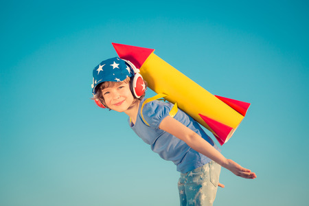 Foto de Happy child playing with toy rocket against summer sky background - Imagen libre de derechos