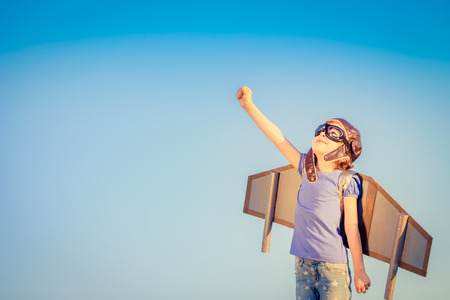 Photo pour Happy child playing with toy wings against summer sky background - image libre de droit