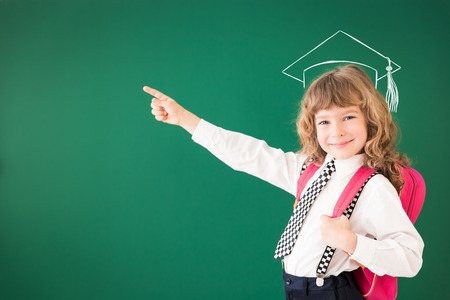 Photo pour School kid in class. Happy child against green blackboard. Education concept - image libre de droit