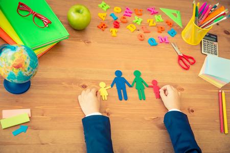 Photo pour Child holding paper family in hands. School items on wooden desk in class. Education concept. Top view - image libre de droit