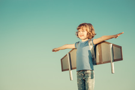 Photo pour Happy child playing with toy wings against summer sky background. Retro toned - image libre de droit