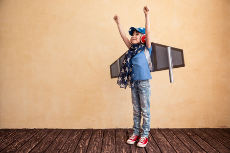 Photo pour Happy child playing at home. Kid having fun with toy paper wings - image libre de droit
