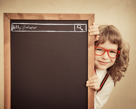 Photo pour School kid in class. Happy child holding blackboard blank. Education concept - image libre de droit