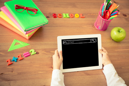 Photo pour Child holding tablet PC in hands. School items on wooden desk in class. Education concept. Top view - image libre de droit