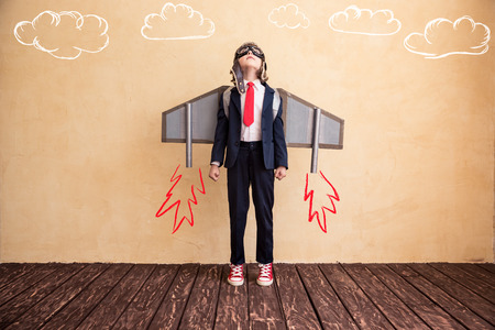 Foto de Portrait of young businessman with toy paper wings. Success, creative and startup concept. Copy space for your text - Imagen libre de derechos
