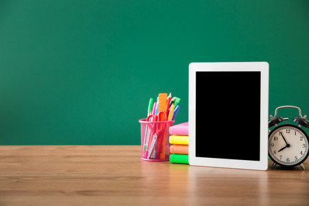 Foto de Tablet PC in classroom against green blackboard. Education concept - Imagen libre de derechos