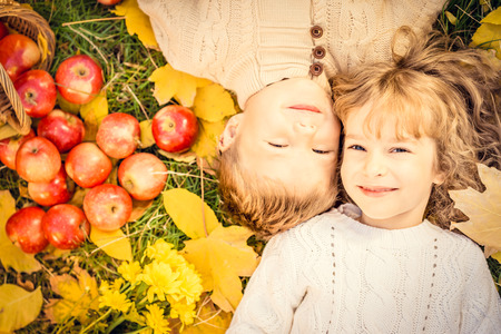 Foto de Happy children lying on fall leaves. Funny kids outdoors in autumn park - Imagen libre de derechos