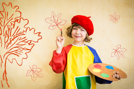 Foto de Happy child playing at home. Drawing autumn theme. Imagination and freedom concept - Imagen libre de derechos