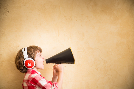 Foto de Kid listen music at home. Hipster child with retro vintage speaker - Imagen libre de derechos