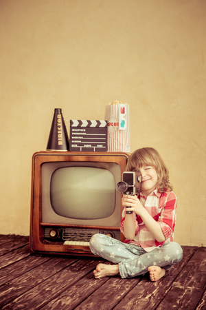 Foto de Child playing at home. Kid making a film with retro camera. Cinema concept - Imagen libre de derechos