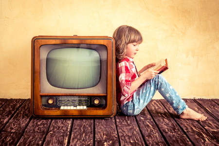 Foto de Child playing at home. Kid reading the book near retro TV. Cinema concept - Imagen libre de derechos