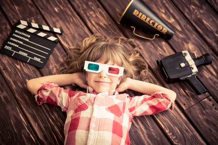 Photo for Child playing at home. Kid with vintage cinema objects. Entertainment concept. Top view - Royalty Free Image