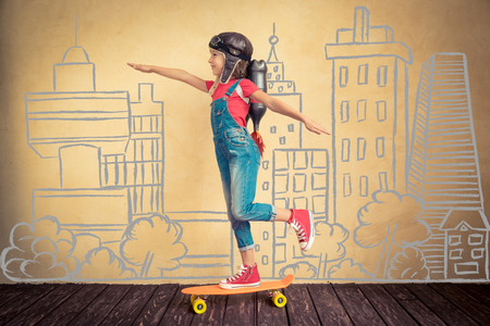 Foto de Kid with jet pack riding on skateboard. Child playing at home. Success, leader and winner concept - Imagen libre de derechos