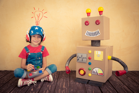 Photo for Happy kid playing with toy robot at home. Retro toned - Royalty Free Image