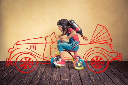 Foto de Kid with jet pack riding bike. Child playing at home. Success, leader and winner concept - Imagen libre de derechos