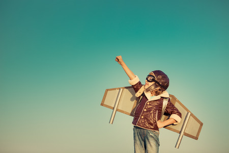 Foto de Kid pilot with toy jet pack against autumn sky background. Happy child playing outdoors - Imagen libre de derechos