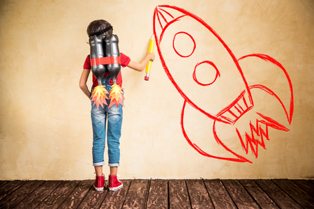 Foto de Kid with jet pack draw sketch on wall. Child playing at home. Success, leader and winner concept - Imagen libre de derechos