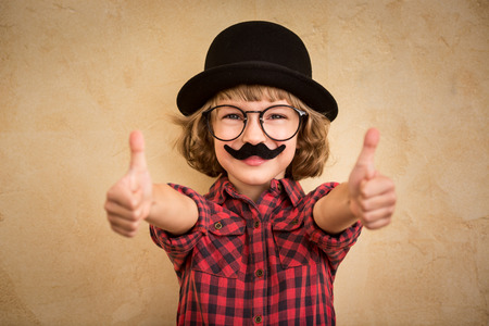 Foto de Funny kid with fake mustache. Happy child playing in home - Imagen libre de derechos