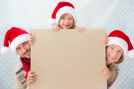 Foto de Happy family holding Christmas card blank. Xmas holiday concept - Imagen libre de derechos