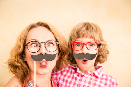 Photo pour Mother and child with fake mustache. Happy family playing in home - image libre de droit