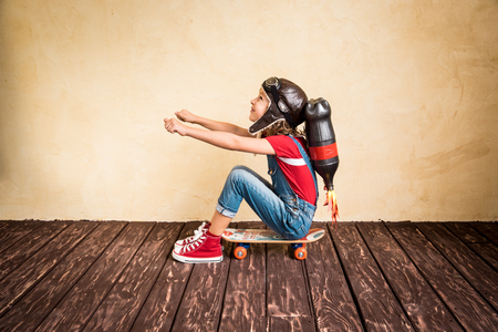 Photo pour Kid with jet pack riding on skateboard. Child playing at home. Success, leader and winner concept - image libre de droit