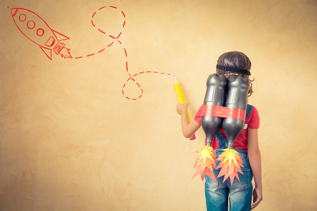 Foto per Kid with jet pack draw sketch on wall. Child playing at home. Success, leader and winner concept - Immagine Royalty Free