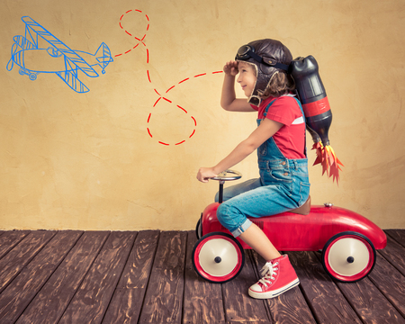 Photo pour Kid with jet pack driving retro toy car. Child playing at home. Success, leader and winner concept - image libre de droit